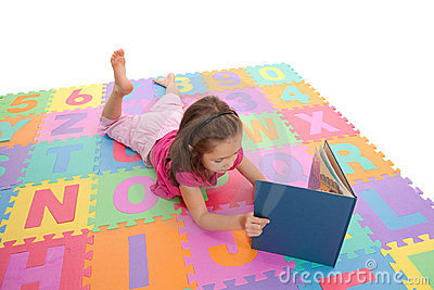 Girl child reading kids book on alphabet mat