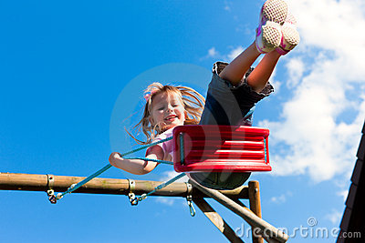 Girl child on swing in the garden