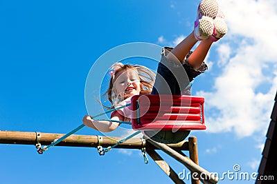 Girl child on swing in the garden