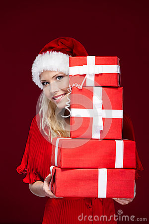 Girl in Christmas cap hands a set of presents