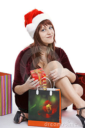 The girl in a Christmas cap with purchases