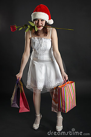 Girl in Christmas cap, with purchases and rose