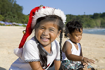 Girl with Christmas hat and boy on beach