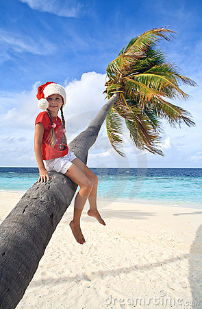 Girl in christmas hat sitting on a palm