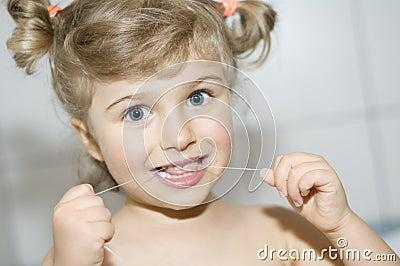 Girl cleaning teeth by dental floss
