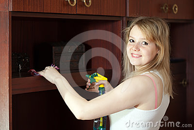 Girl cleans furniture at home