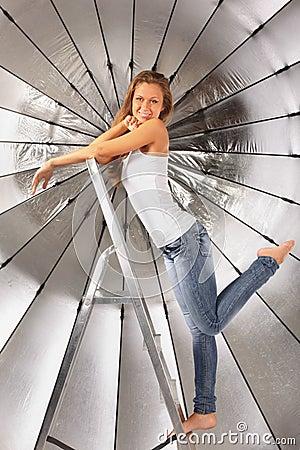 Girl climbed on ladder near silver umbrella