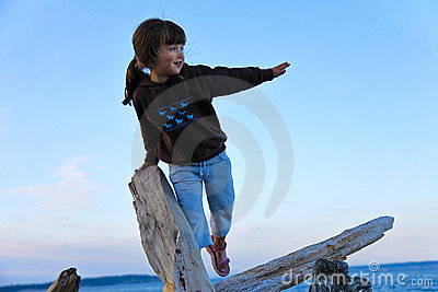 Girl Climbing on Driftwood at the Beach