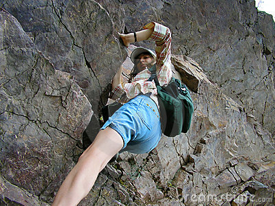 Girl climbing rocks, striving to the peak of the mountain