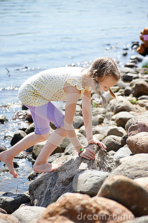Girl climbing on stones by coast