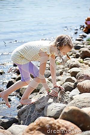 Girl climbing on stones by coast