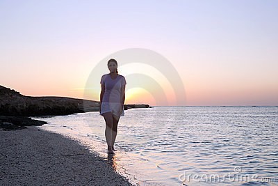 Girl at coast sea  during  sunrise
