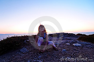 Girl on coastline at sunset