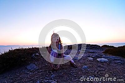 Girl on coastline at sunset