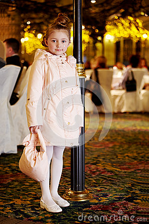Girl in coat stands near to lamp post