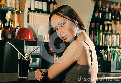 Girl with cocktail sitting in bar