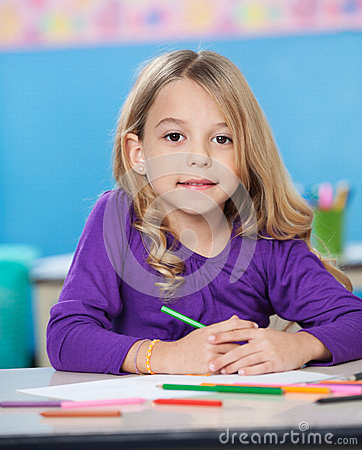 Girl With Colored Sketch Pens And Paper At Desk
