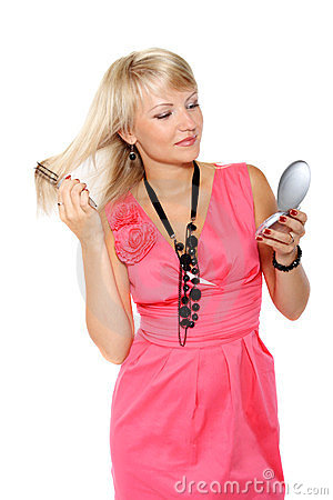 Girl combing her hair before a mirror