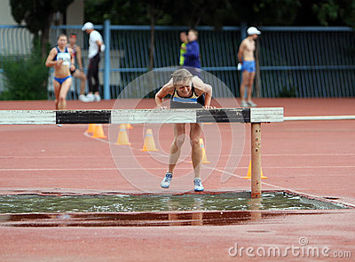 Girl compete in the 3.000 Meter Steeplechase Editorial Photo