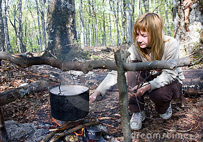 Girl cooking food on fire in camp