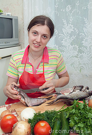 Girl is cooking a fresh  fish