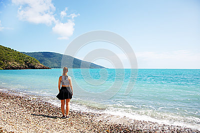 Girl on coral beach looking out to sea