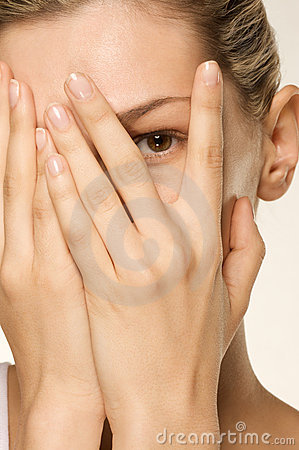 Girl covering her face with hands one eye exposed