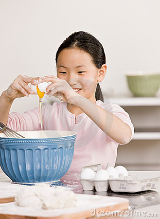 Girl cracks eggs into bowl for baking project