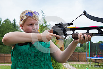 A girl with a crossbow aiming at a target