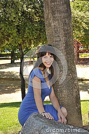 Girl crouching next to tree