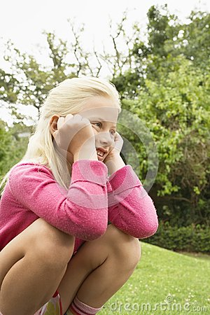 Girl Crouching In Park