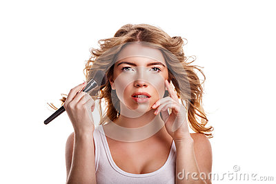 girl with curly hair straightens makeup brush stock photo