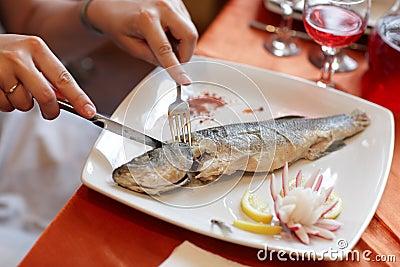 Girl cuts dorado fish