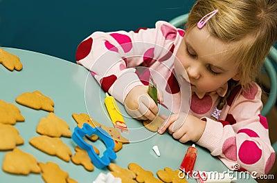 Girl decorating Xmas cookies