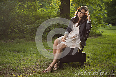 Girl deep in thoughts sitting on a bench in park