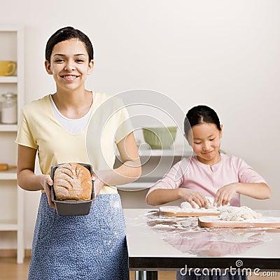 Girl displays baked loaf of bread