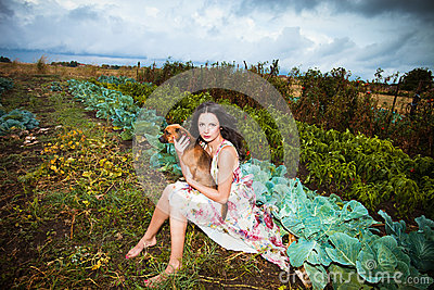 Girl with dog  in autumn vegetable garden