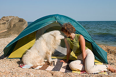 Girl with dog sitting near of a tent