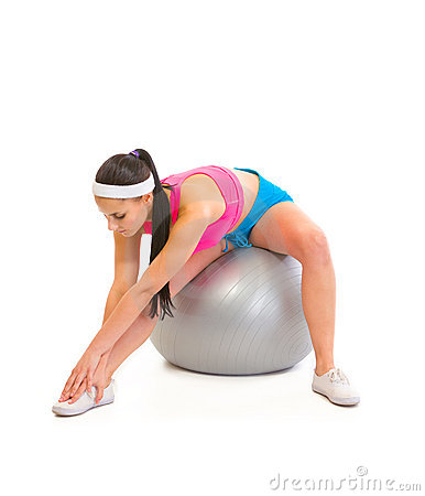 Girl doing stretching exercises on fitness ball
