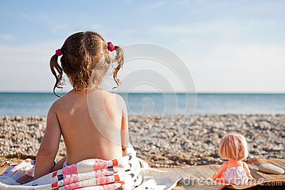 Girl and doll on the beach