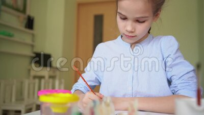 Girl drawing with brush and paints. At the centre for studies of children stock video