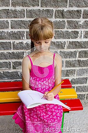 Girl draws album sitting bench 5055