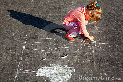 Girl draws painting line a chalk on asphalt