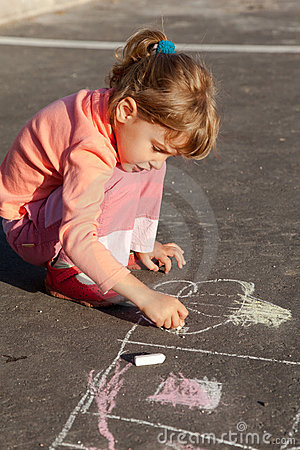 Girl draws painting line house a chalk on asphalt