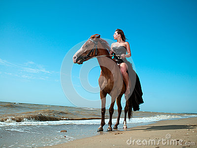 Girl in a dress on a horse by the sea