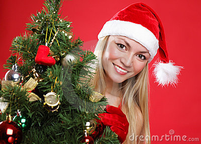 Girl dressed as Santa and a christmas fur-tree
