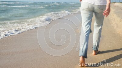 Girl dressed in jeans and white blouse walking along sea shore stock video footage