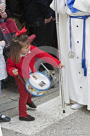 Girl dressed in red with a toy drum looking in front of a Nazarene Editorial Stock Image