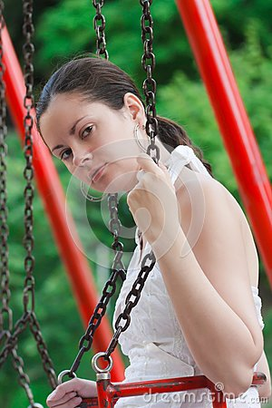 Girl dressed in white ride the swing