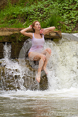 A girl dressed in white, sitting by a waterfall.
